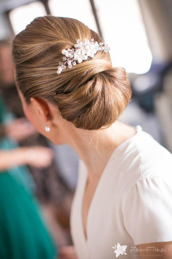 Bridal chignon hairstyle with white hairpiece at Willowdale Estate in Topsfield, MA www.willowdaleestate.com