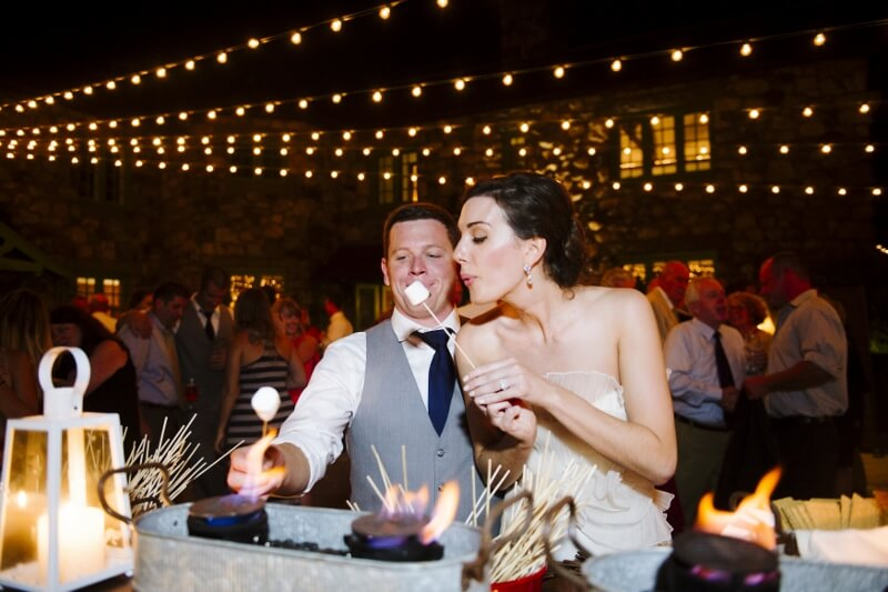 Summer bride and groom share a s'mores bar moment under the bistro lights at Willowdale Estate, a wedding and event venue north of Boston, Massachusetts - willowdaleestate.com
