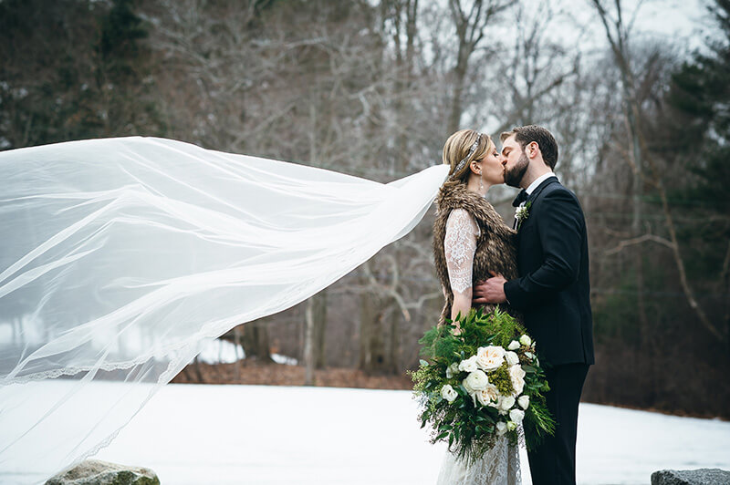 Bride with cathedral length veil and faux fur vest attire for winter wedding at Willowdale Estate in Topsfield, MA willowdaleestate.com
